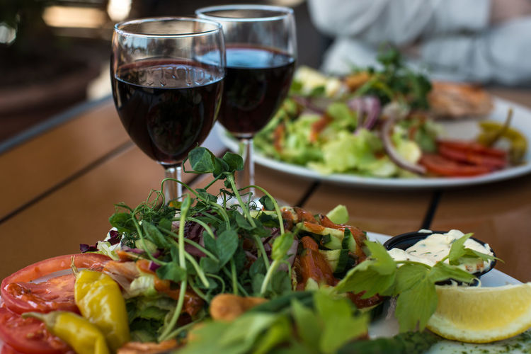 Close-Up Of Wine And Salad On Table