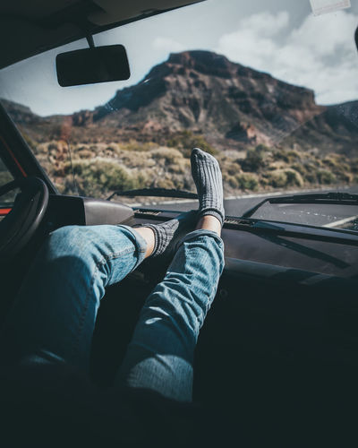 Low Section Of Person Sitting In Car On Road