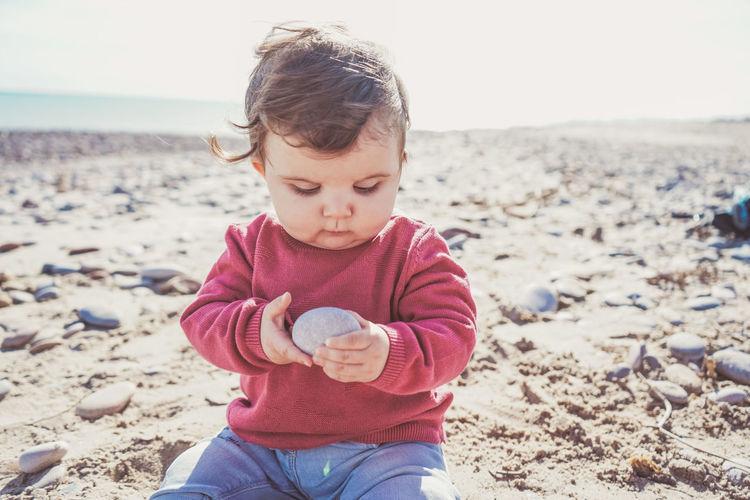 Cute boy holding sand at beach