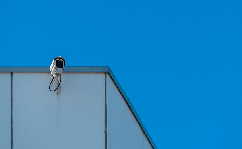 Low angle view of metal against building against clear blue sky