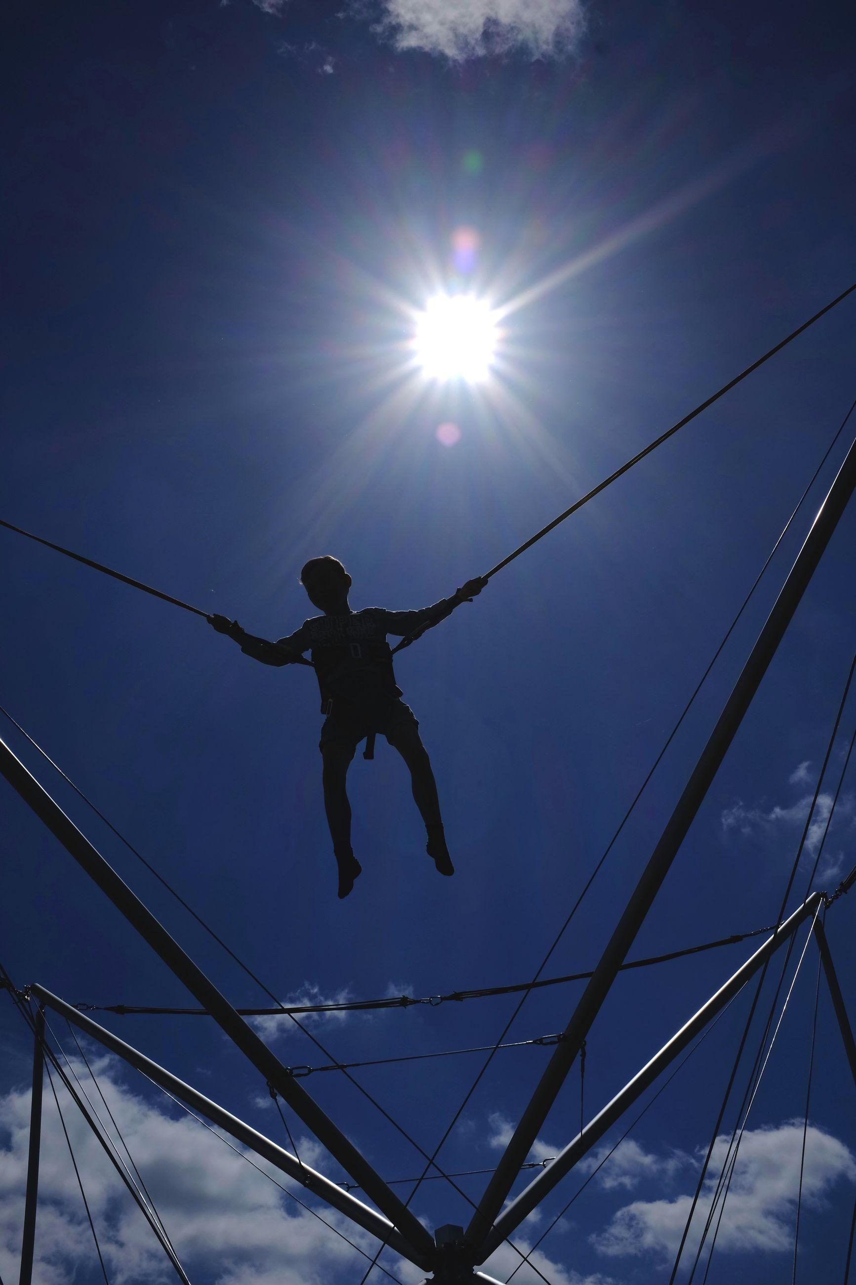 low angle view, leisure activity, sky, lifestyles, enjoyment, sun, fun, transportation, mid-air, extreme sports, sunlight, full length, lens flare, men, sunbeam, blue, silhouette, adventure