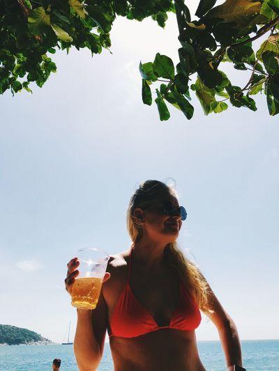 Woman in bikini drinking beer at beach against sky