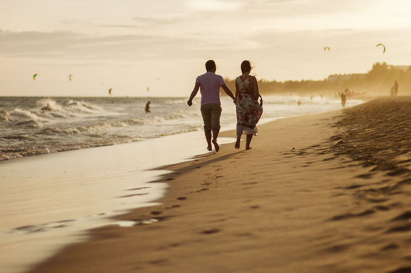 Rear view of couple walking at beach against sky