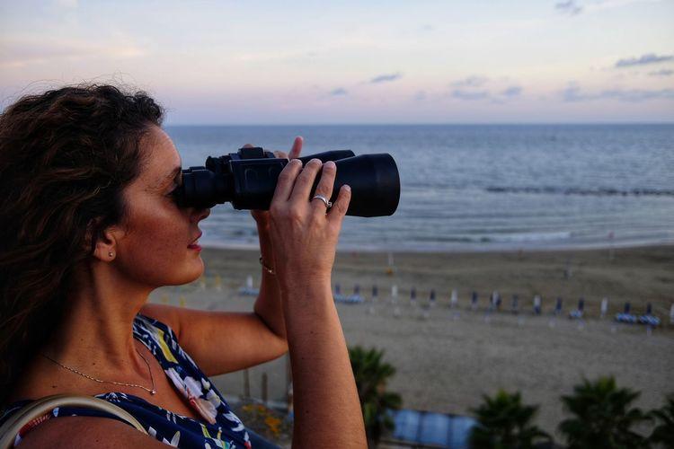 Woman looking through binoculars standing against beach during sunset