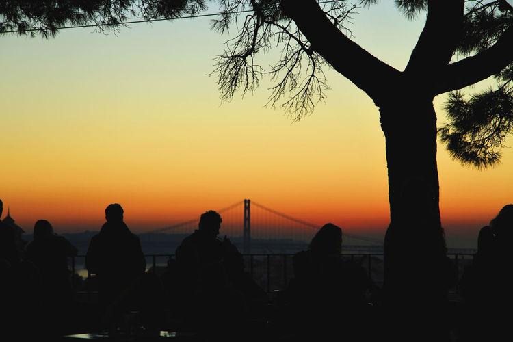 Silhouette people at miradouro da graca against april 25th bridge during sunset