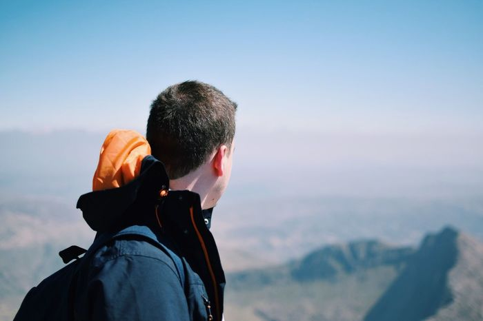 Adventure Backpack Beauty In Nature Clear Sky Day Exploration Focus On Foreground Headshot Hooded Shirt Leisure Activity Lifestyles Looking At View Men Mountain Nature One Man Only One Person Only Men Outdoors Real People Rear View Scenics Sky Standing Warm Clothing