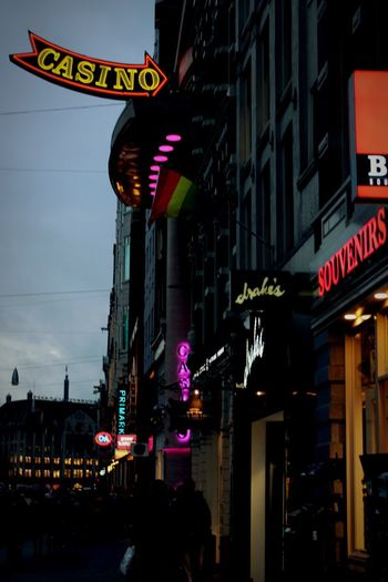Illuminated Text Western Script Building Exterior Architecture Communication Night Built Structure Neon Large Group Of People Low Angle View Outdoors Advertisement Travel Destinations City Life Nightlife City Sky People Blurry Blurred Motion Adult Amsterdam