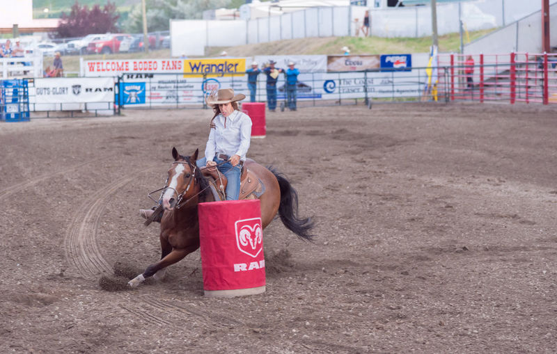 Williams Lake, British Columbia/Canada - June 30, 2016: horse and rider cut around the second barrel at the 90th Williams Lake Stampede, on of the largest stampedes in North America. 90th Williams Lake Stampede Arena British Columbia, Canada Canadian Professional Rodeo Association Horse And Rider Racing Rodeo Travel Woman Barrel Race Candid Competition Country Western Cowgirl Documentary Editorial  Extreme Sports Horse Horseback Riding Professional Rodeo Race Stampede Stampede Grounds Tourism Western Dress