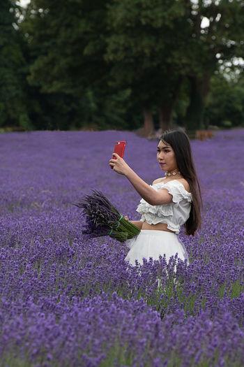 Woman standing on purple flower on field