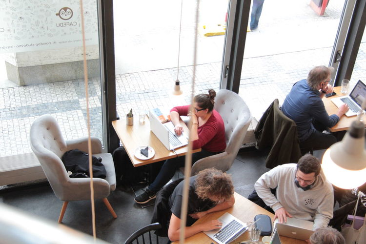 Group Of People Sitting Table Men High Angle View Window Adult Real People Women Indoors  Seat Group Males  Day People Communication Casual Clothing Chair Wireless Technology Studying Using Laptop Business Working Coworkingspace Technology