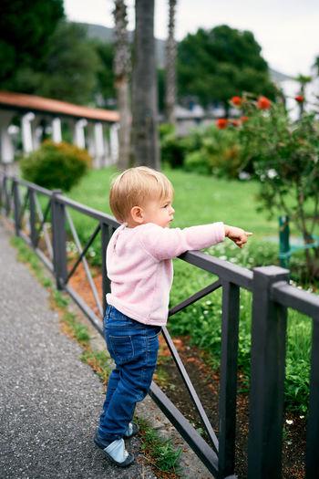 Full length of cute boy standing on railing
