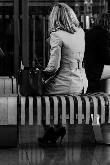 Rear view of woman sitting with purse on bench at hamburg airport