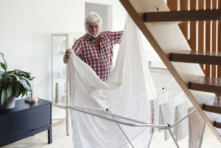 Senior man folding white sheet for drying on rack in living room