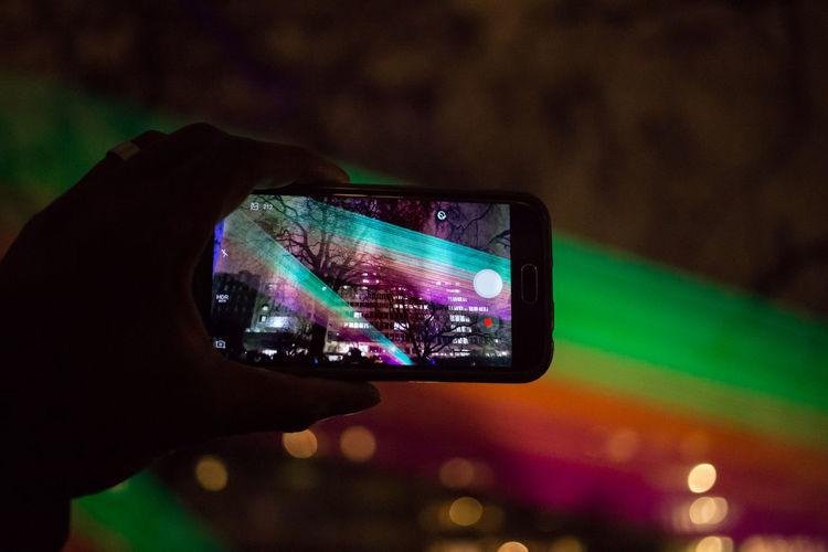 Close-up of man photographing illuminated smart phone at night