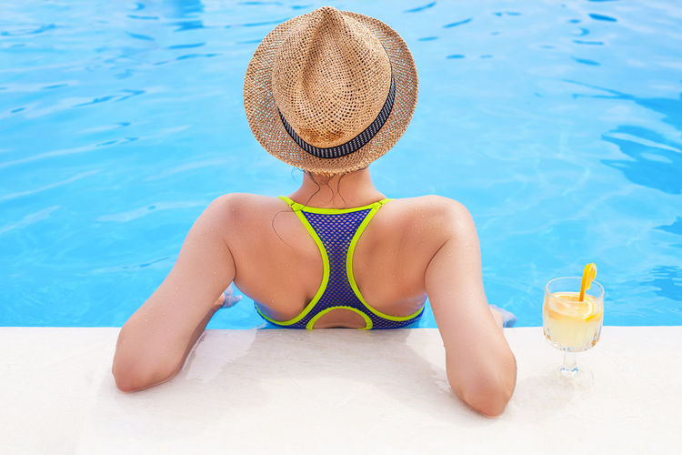 Midsection of woman wearing hat against swimming pool