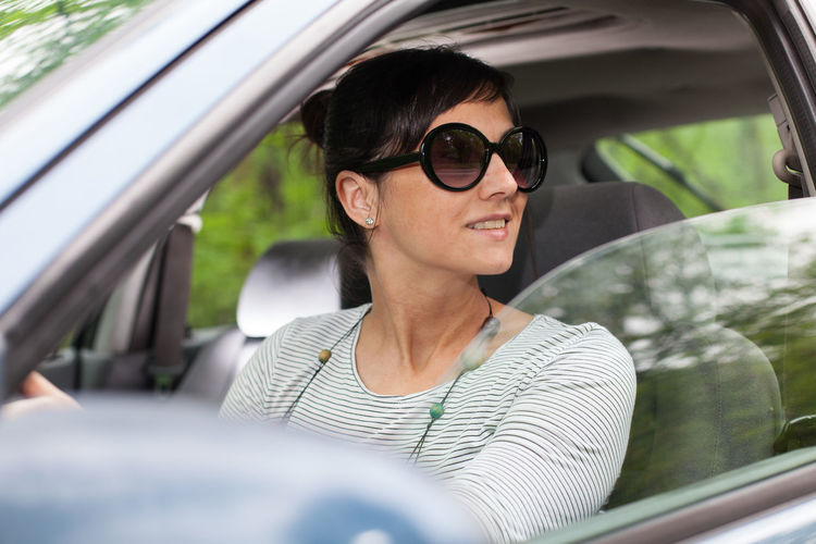 Close-Up Of Woman Wearing Sunglasses While Driving Car