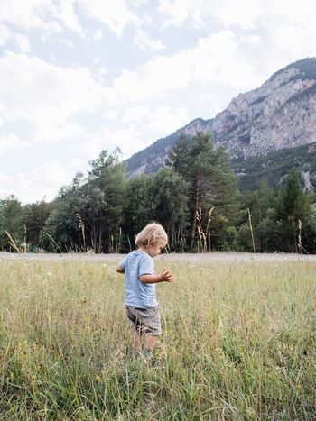 Childhood One Person Blond Hair Nature Day Casual Clothing Standing Grass Full Length Outdoors Child Leisure Activity One Boy Only Sky Mountain People Beauty In Nature Boys Children Only Tree