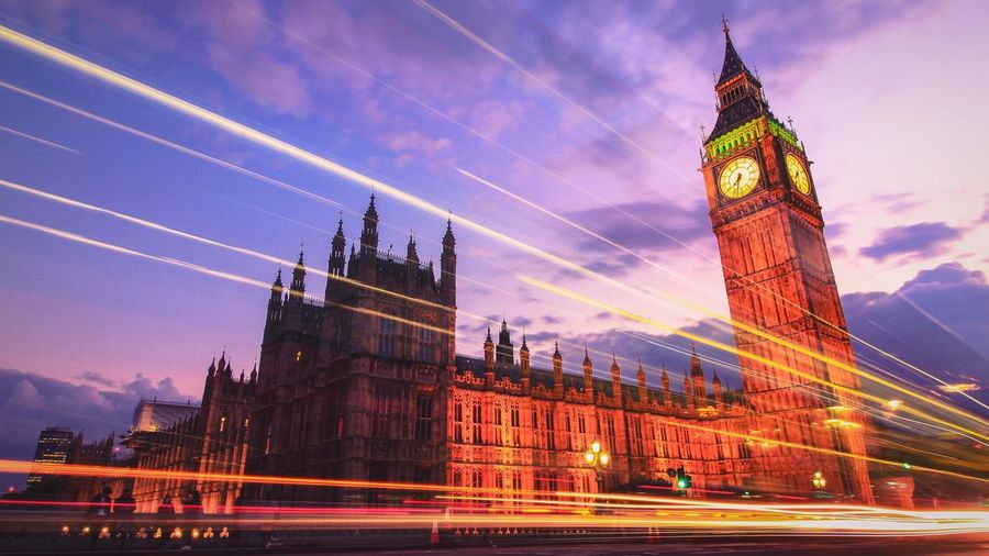 Light trails by illuminated big ben against sky at dusk