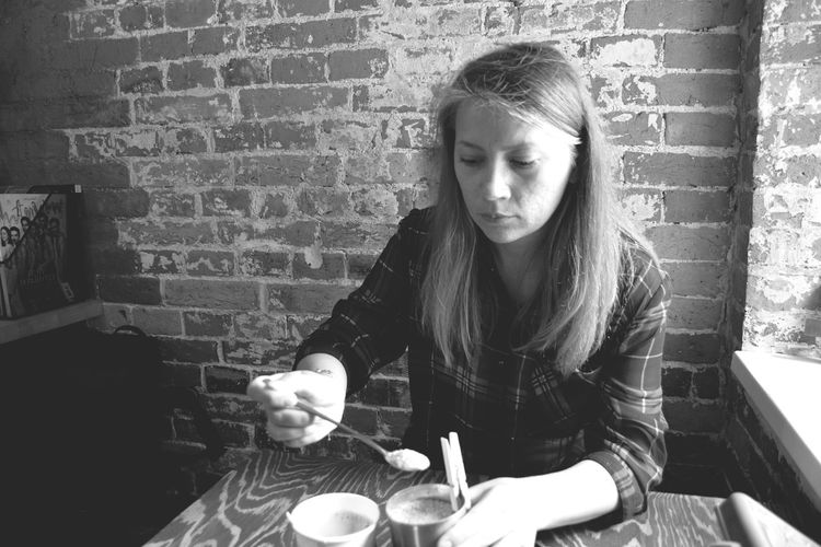 Woman Having Coffee At Table Against Wall