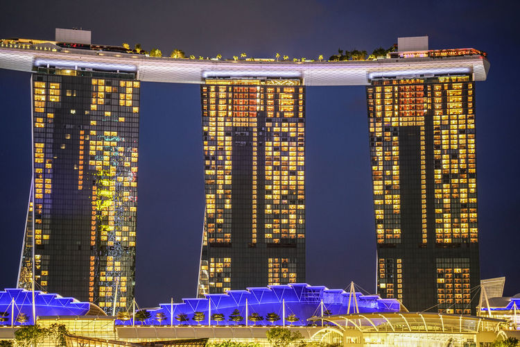 Low angle view of illuminated buildings against sky at night