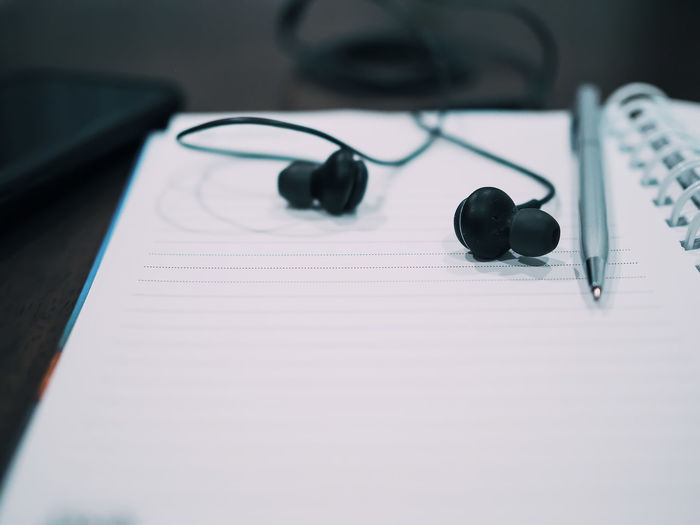 High angle view of in-ear headphones and pen on notebook