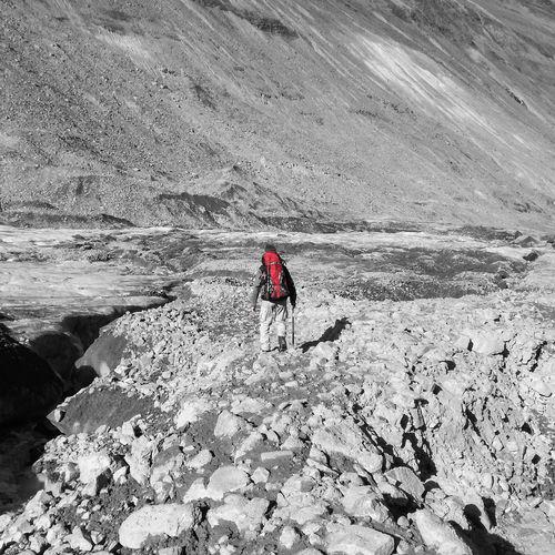 Rear view of backpack male hiker walking on field against mountain