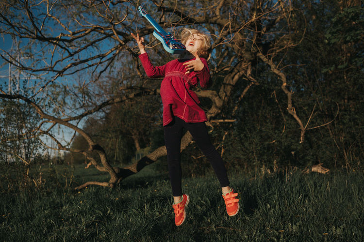 Full length of girl playing with bare trees