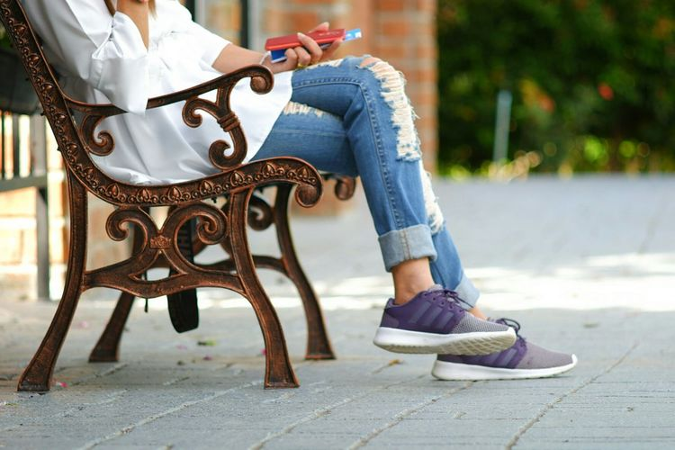 Low section of woman sitting on bench in park