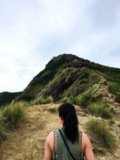 Rear view of mature woman looking at mountain against sky