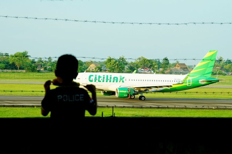 Rear view of man on airport runway against sky