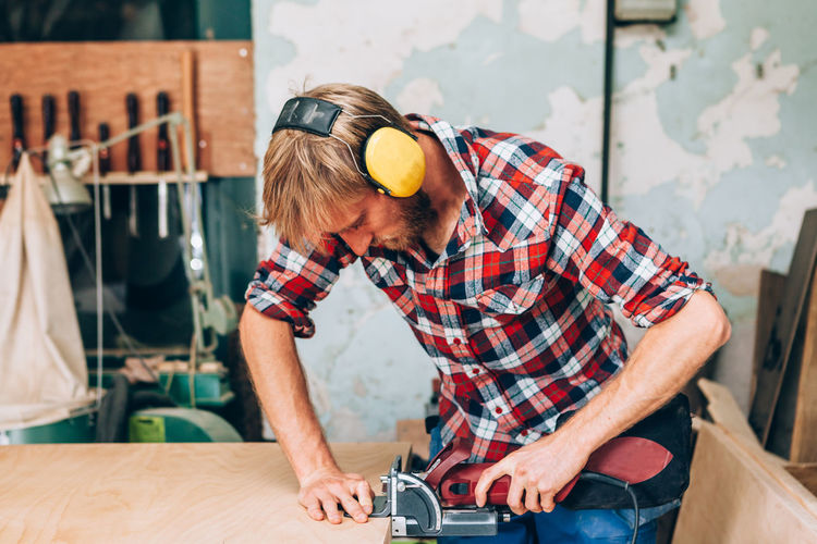 carpenter milling a wooden board in his workshop Construction Headphones Workshop Adult Art And Craft Carpenter Casual Clothing Indoors  Industry Job Males  Men Milling Milling Machinery Occupation People Real People Skill  Standing Tool Wood - Material Working Workshop Young Adult Young Men