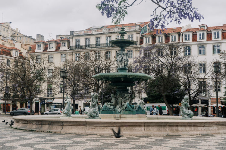 Fountain Portugal Square Statue Architecture Bird Building Building Exterior Built Structure City Life Flying Incidental People Lisbon Outdoors Sculpture Statue Travel Destinations