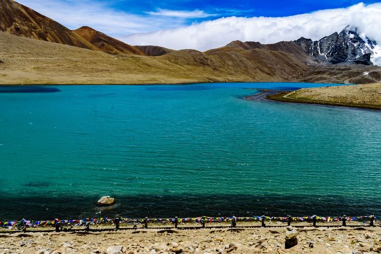 Scenic view of turquoise lake by mountain range