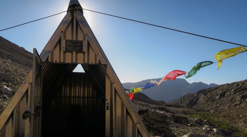 Mountain hut with flags attached to it blowing in the wind Adventure Beauty In Nature Cabin Door Exploration Explore Flag Hike Hiker Hiking Hut Landscape Landscape_Collection Mountain Mountain Range Nature Outdoor Photography Outdoors Rock - Object Scenics Summer Travel View Wilderness