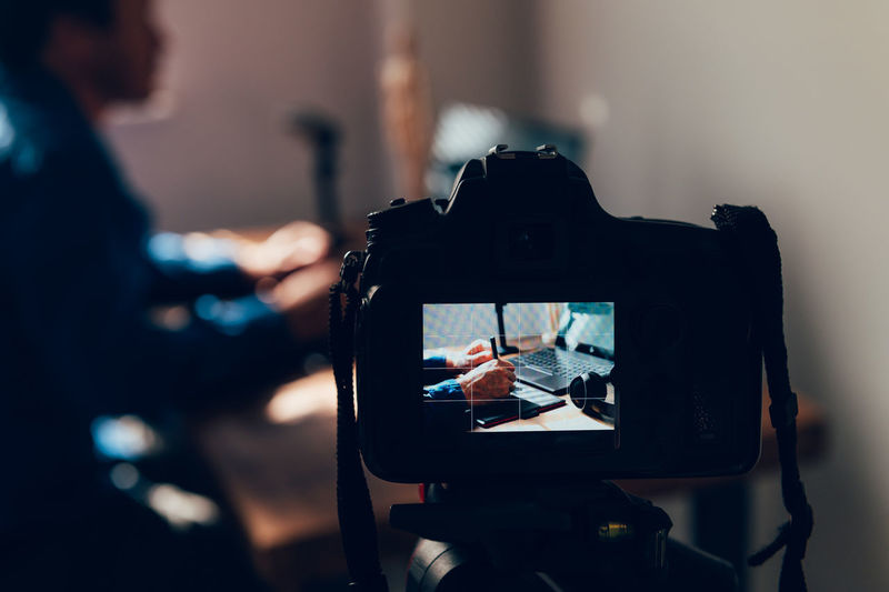 Close-up of camera photographing man working at home