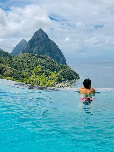 Rear view of shirtless man in infinity pool looking at sea
