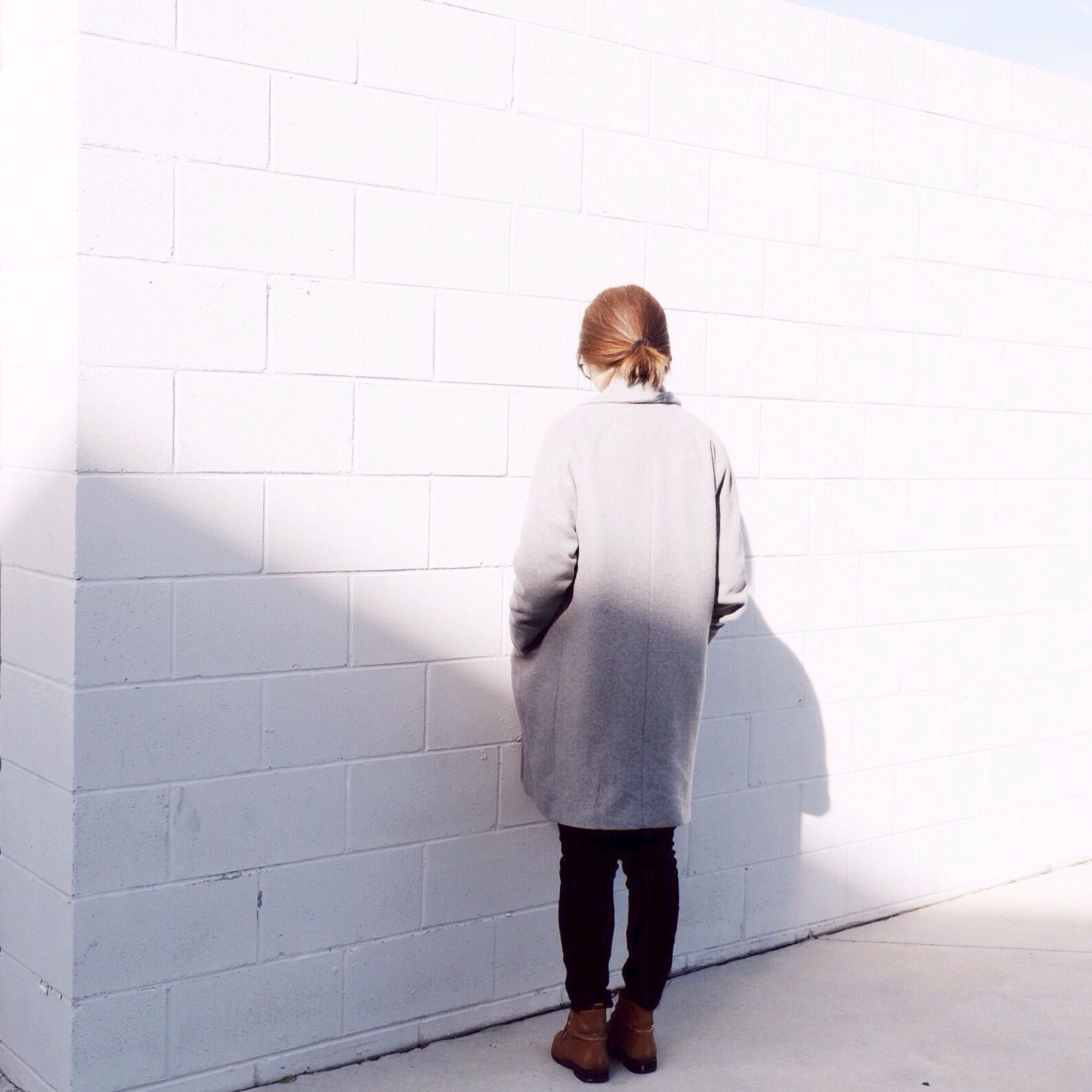 standing, casual clothing, lifestyles, rear view, full length, wall - building feature, walking, young adult, leisure activity, architecture, person, built structure, front view, wall, young women, three quarter length, men, brick wall