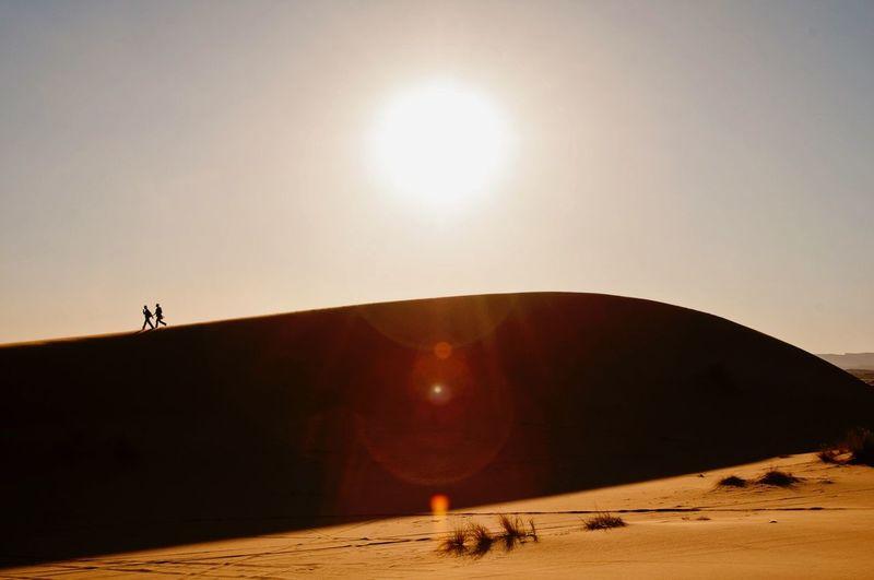 People running on sand dune