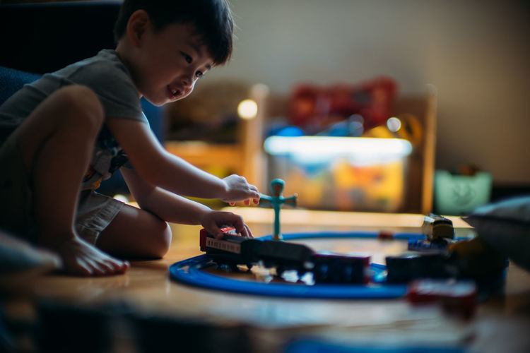 Side view of boy playing with miniature train at home