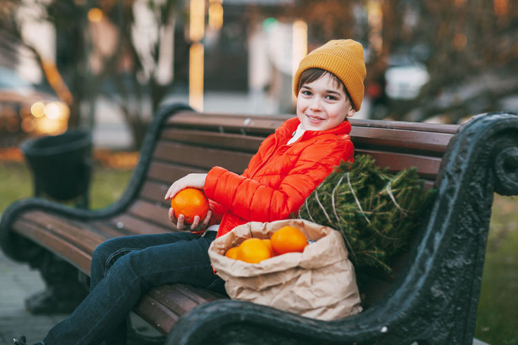 A boy in a bright orange jacket and a fashionable yellow hat sits on a bench, laughs, throws oranges