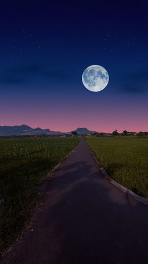 Scenic view of road amidst field against sky at night
