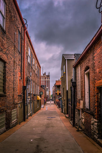 Street Amidst Old Houses Against Cloudy Sky