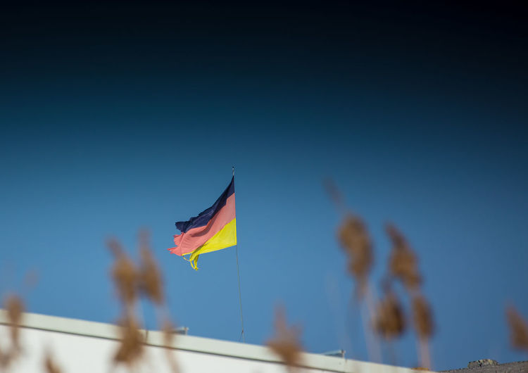 A waving german flag, which is not in its best shape. Symbolic. Blur Europe European  Flag Freedom German Germany Government Identity National Nature Outdoors Patriotism Sky Summer Symbol Travel
