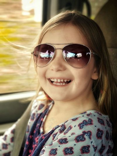 Portrait of cheerful girl wearing sunglasses in car