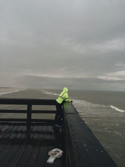 Man at pier during bad weather