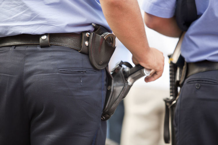 Midsection Of Security Staff With Handguns