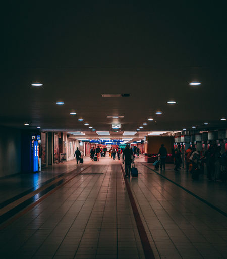 Airport Airport Runway Architecture Built Structure Ceiling Crowd Direction Flooring Group Of People Illuminated Indoors  Large Group Of People Lifestyles Light Lighting Equipment Men Public Transportation Rail Transportation Real People The Way Forward Tile Tiled Floor Transportation Walking Women