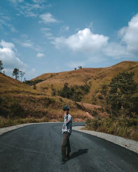 Men walking on road against sky