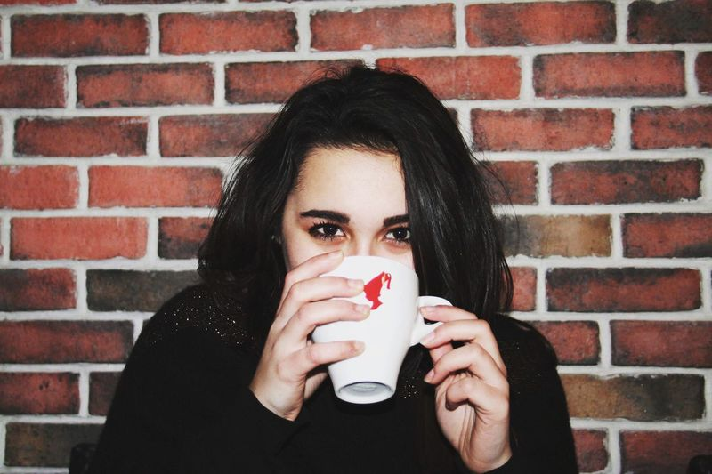 Portrait Of Young Woman Drinking Coffee Against Brick Wall