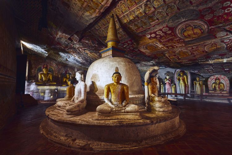 Dambulla, Sri Lanka - January 12, 2019: Statues and paintings inside of largest and best preserved cave temple complex in Sri Lanka. Golden Temple of Dambulla on January 12, 2019. Cave Rock Temple - Building Dambulla Sri Lanka Ancient Buddha Buddhism Art Statue Painting Architecture UNESCO World Heritage Site Praying Religion Landmark Famous Place Tourism Meditation Indoors  Architecture History Travel Destinations Indoors  Spirituality